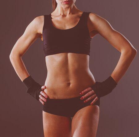 Muskulöse junge Frau, die auf grauem Hintergrund steht. Muskulöse junge Frau Standard-Bild