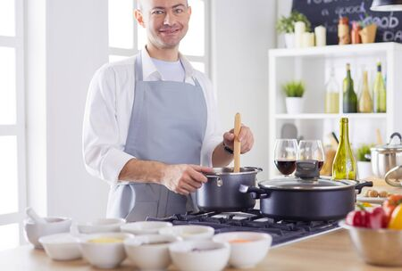 Handsome man is cooking on kitchen and smiling