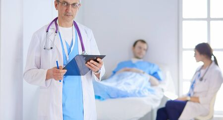 Doctor holding folder in front of a patient and a doctor