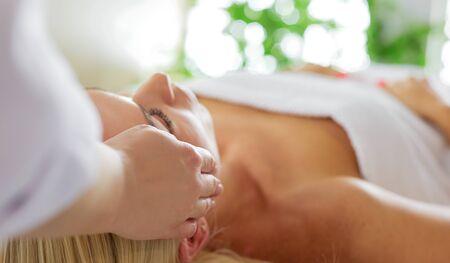 Young woman enjoying massage in spa salon.