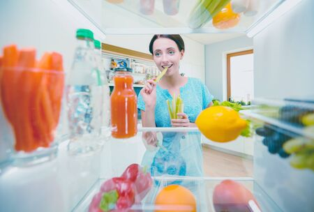 Young woman taking fresh healthy vegetables from the fridge and preparing lunch, diet and lifestyle concept 写真素材