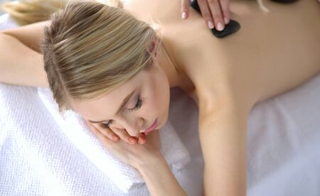 Young woman lying on a massage table,relaxing with eyes closed. Woman. Spa salon Фото со стока