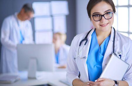 Vrouwelijke arts die tabletcomputer gebruikt in de ziekenhuislobby
