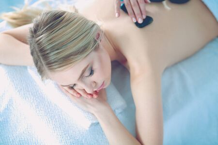 Young woman lying on a massage table,relaxing with eyes closed. Woman. Spa salon.