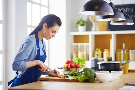 Young woman cutting vegetables in kitchen at home Archivio Fotografico