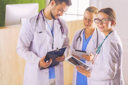 Doctors using a tablet in hospital standing in office