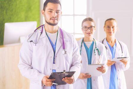 Grupa lekarzy i pielęgniarek stojących na sali szpitalnej