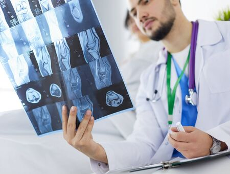 Attractive doctor examining an x-ray and smiling at the camera Reklamní fotografie