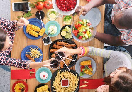 Draufsicht der Gruppe von Leuten, die zusammen beim Abendessen am Holztisch sitzen. Essen auf dem Tisch. Die Leute essen Fast Food.