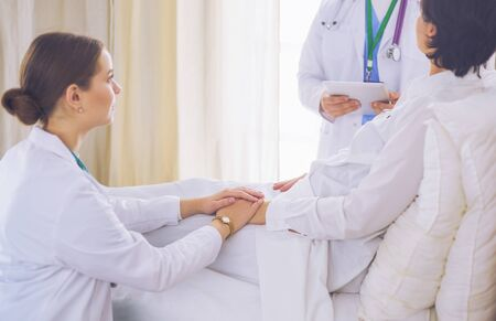 medical doctor holing senior patients hands and comforting her
