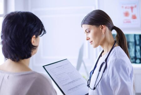 Beautiful female doctor explaining medical treatment to a patient Stock Photo