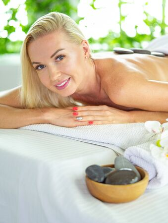 Beautiful young woman with eyes closed receiving hot stone massage at salon spa