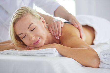 Young woman enjoying massage in spa salon