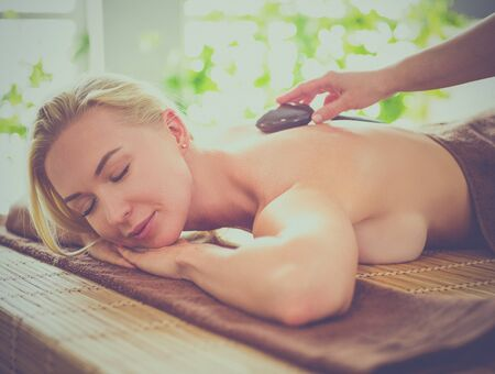 Young woman getting hot stone massage in spa salon. Beauty treatment concept Stock Photo