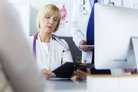 Female doctor sitting at table with laptop, working