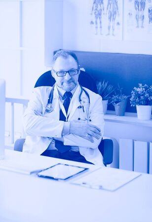 Portrait of senior doctor in office sitting at the desk Stock Photo