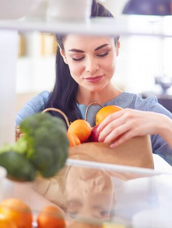 Smiling woman taking a fresh fruit out of the fridge, healthy food concept Stock fotó