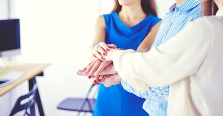 Business colleagues stacking hands together at office