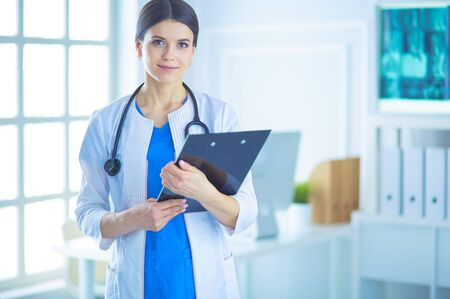 Young smiling female doctor with stethoscope holding a folder at doctors office
