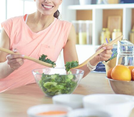 Smiling young woman mixing fresh salad in the kitchen. Banco de Imagens