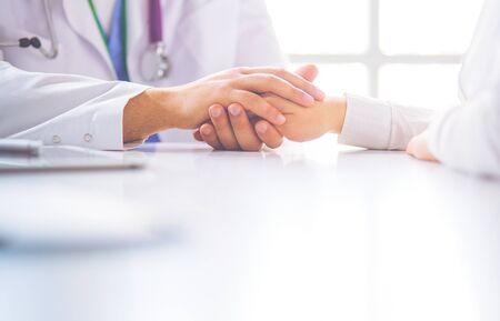 Nahaufnahme von Stethoskop und Papier auf dem Hintergrund von Arzt- und Patientenhänden, Standard-Bild