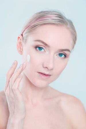 The beautiful young girl with a clean fresh skin touches with a hand a cheek Standard-Bild