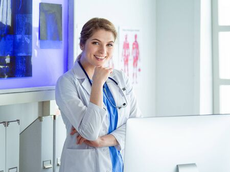 Young woman medic in white uniform standing in clinics office Banco de Imagens