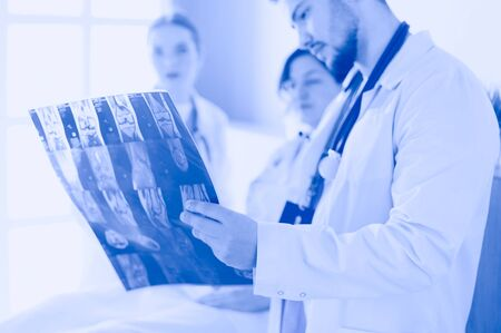 Medical team discussing diagnosis of x-ray image in office