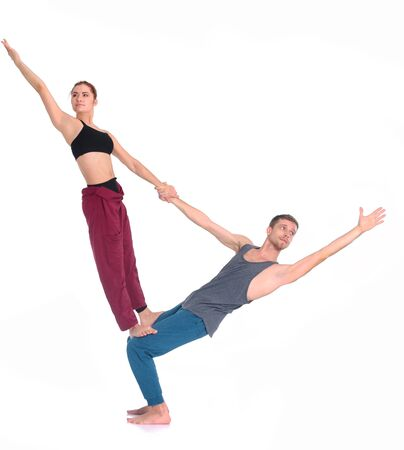 Young athletic couple practicing acroyoga. Balancing in pair.