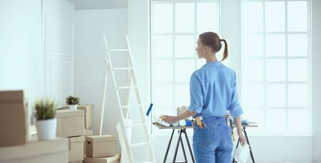 Happy woman paints wall with roller at home.
