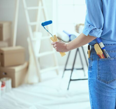 Pretty woman painting interior wall of home with paint roller.