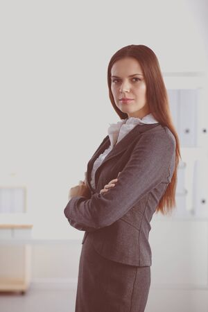 Portrait of business woman standing with crossed arms in office.