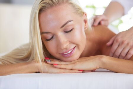 Young and beautiful girl relaxing in spa salon. Massage therapy over seasonal summer or spring background