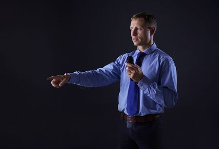 Man holding a microphone while pointing his finger at you