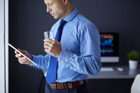 Smiling businessman with touchpad standing at workplace in office 免版税图像