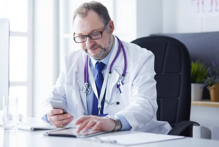 Portrait of senior doctor in office sitting at the desk