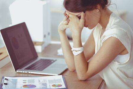 Retrato de mujer de negocios joven cansada con ordenador portátil