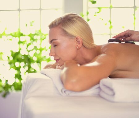 Beautiful young woman relaxing during full body massage at spa