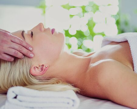 Young woman getting spa massage treatment at beauty spa salon. Facial beauty treatment.