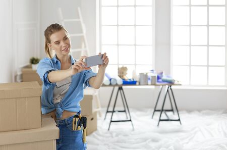 Happy young woman taking selfie while smiling cheerfully, having moved into a new flat