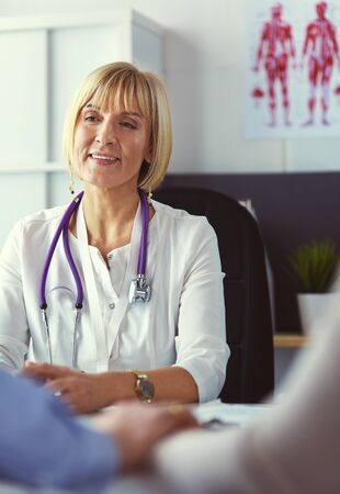 Couple talking to medical specialist, sitting at doctors office Imagens