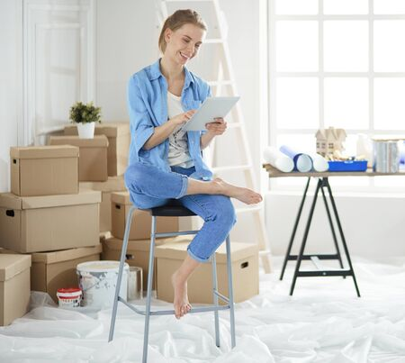 Young woman sitting at home and buying new furniture over the Internet using a tablet computer
