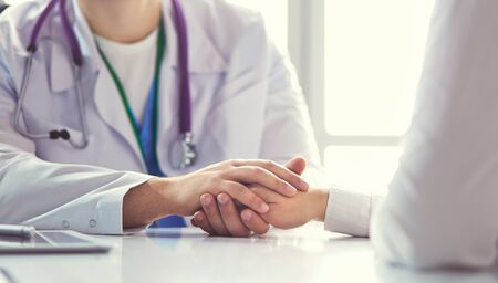 Close-up of stethoscope and paper on background of doctor and patient hands,