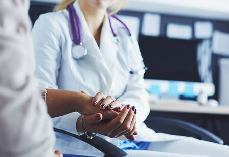 Doctor or nurse holding elderly lady's hands.