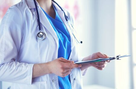 Woman doctor standing with folder at hospital.