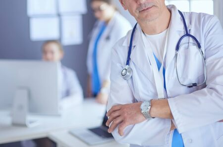 Doctor holding folder in front of a patient and a doctor.