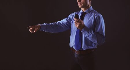 Man holding a microphone while pointing his finger at you.