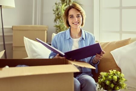 Young woman moving out and packing cardboard box