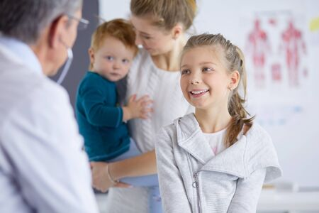 Girl and doctor with stethoscope listening to heartbeat
