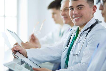 Équipe médicale assise et discutant à table